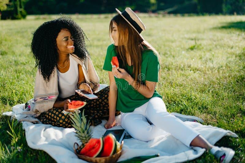 2 привлекательных молодых мульти-этнических подруги счастливо говорящ и ели арбуз на пикнике Очаровывать стоковые изображения