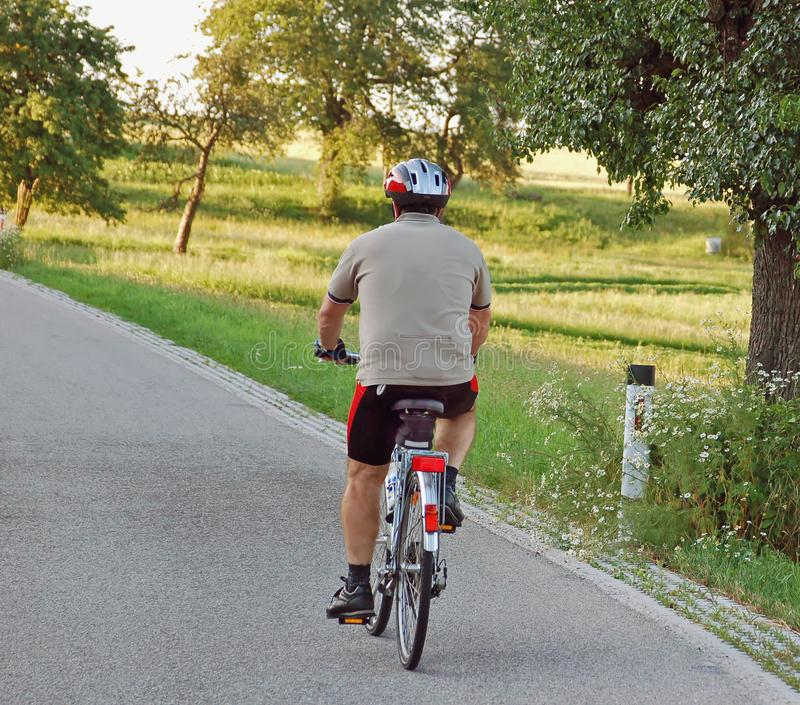 Привод велосипедиста вверх по холму стоковое фото