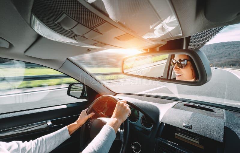 Привод женщины автомобиль отражает в заднем зеркале взгляда стоковая фотография