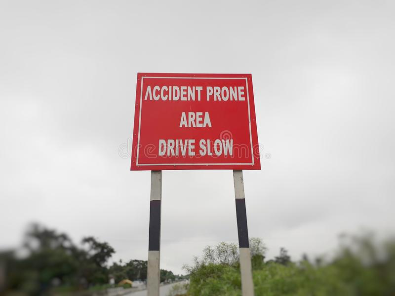Привод медленный, доска на шоссе, обочина знака зоны аварии прональная стоковая фотография