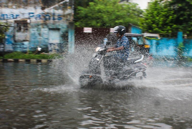Привод регулярных пассажиров пригородных поездов вдоль затопленной улицы стоковые изображения rf