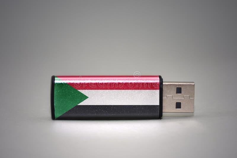 Привод вспышки Usb с национальным флагом Судана на серой предпосылке стоковые изображения