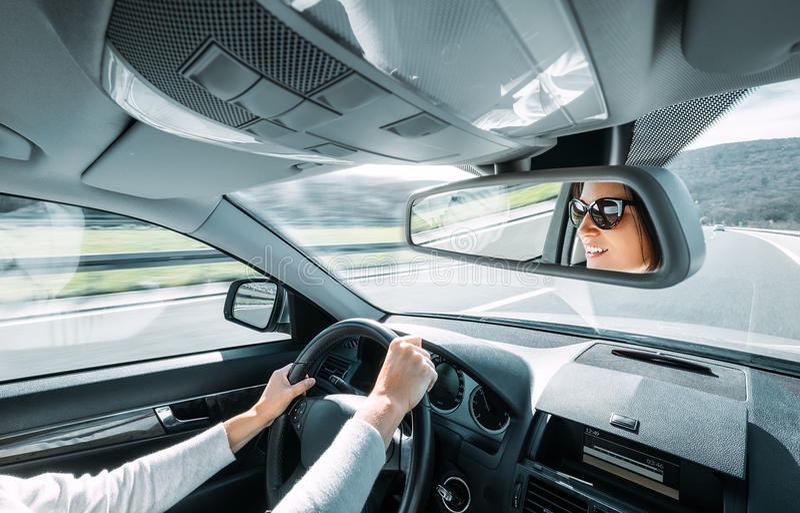 Привод женщины автомобиль отражает в заднем зеркале взгляда стоковые изображения rf