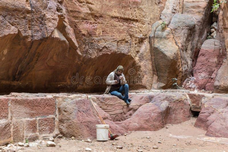Привратник бедуина сидит в нише в утесе и остатках на каньоне водя к Petra - столице королевства Nabatean в вадях стоковое изображение