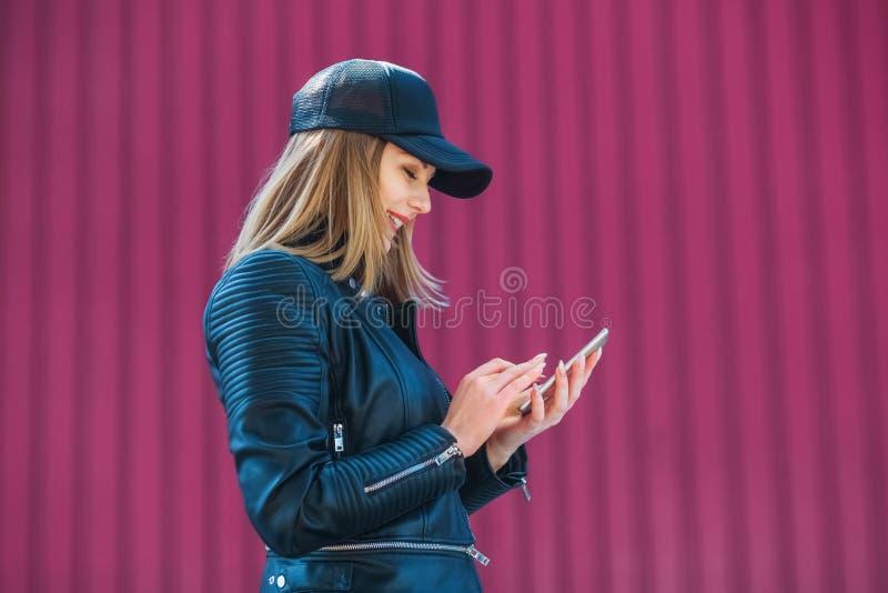 Привлекательная белокурая девушка в кожаной черных куртке и крышке, занимаясь серфингом интернет на мобильном телефоне стоковые изображения