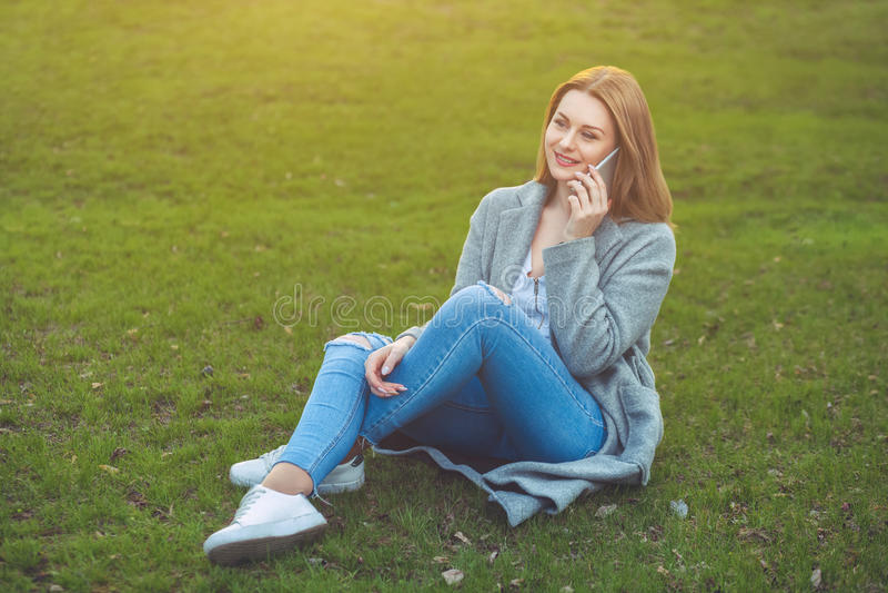 Привлекательная белокурая девушка говоря на мобильном телефоне сидя на траве стоковые изображения rf