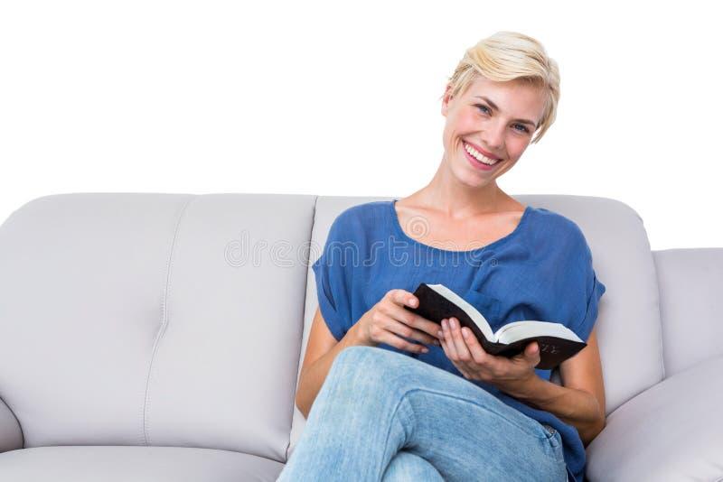 Привлекательная белокурая женщина читая книгу на кресле стоковые изображения
