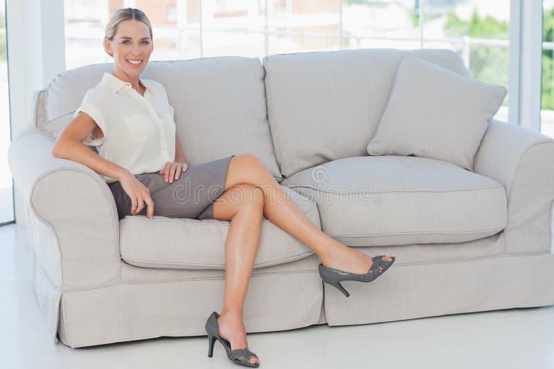 Привлекательная белокурая коммерсантка представляя сидеть на софе стоковое фото rf