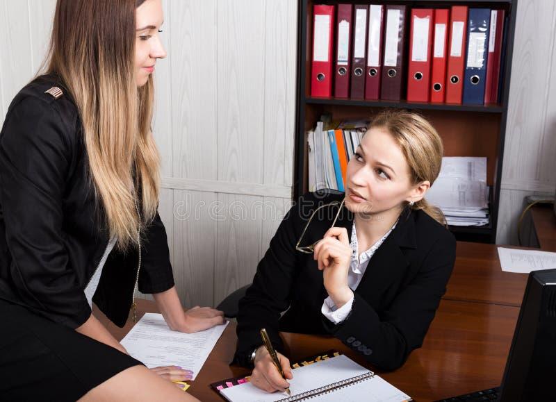 Привлекательная бизнес-леди работая с документами в офисе женщина в деловом костюме сидя на таблице и знаке стоковое фото