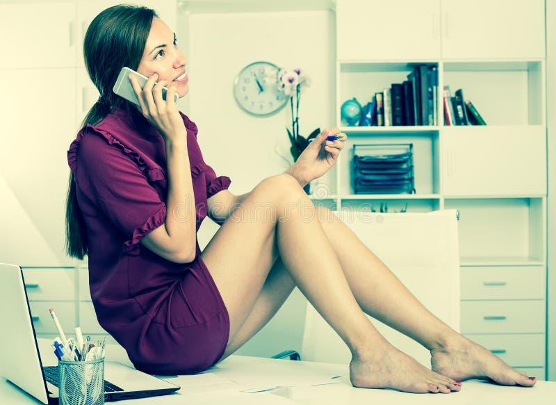 Привлекательная бизнес-леди сидя на работая столе на офисе стоковые изображения