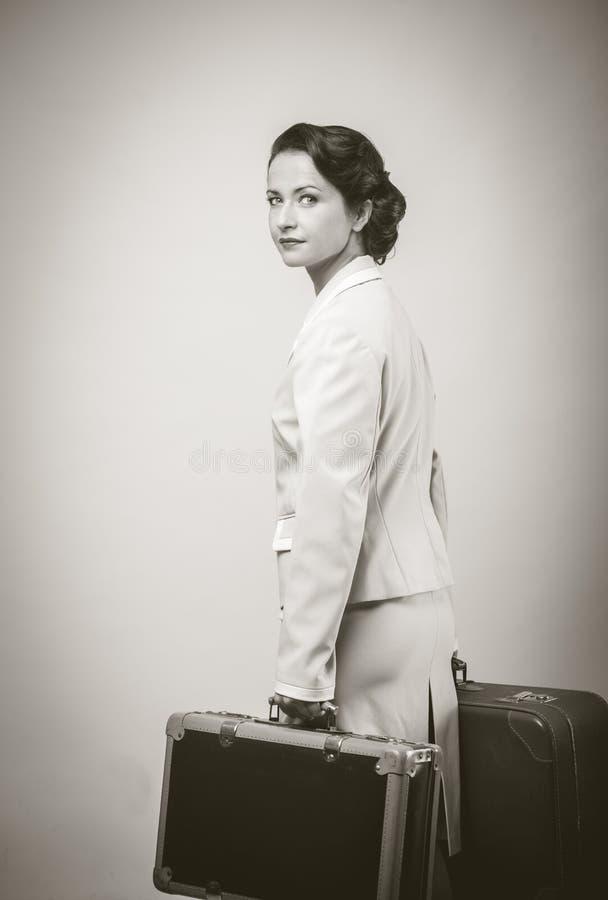 Привлекательная винтажная женщина с чемоданами стоковая фотография