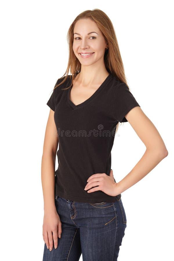 Привлекательная девушка в усмехаться футболки и джинсов стоковое изображение