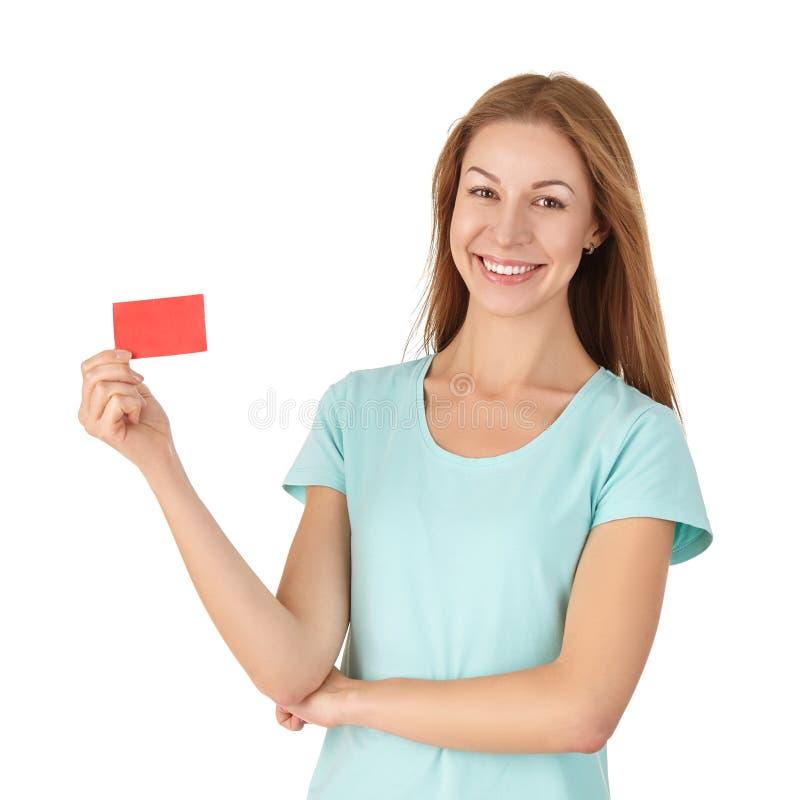 Привлекательная девушка в футболке держа карточку и усмехаться стоковые изображения rf