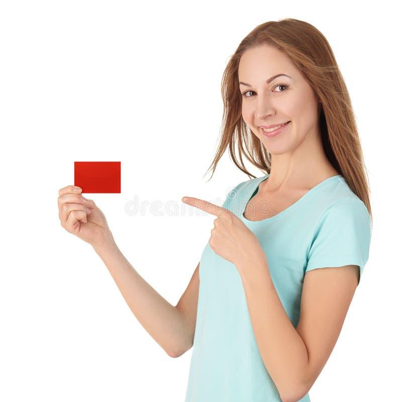 Привлекательная девушка в футболке держа карточку и усмехаться стоковые фото