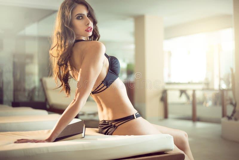 Привлекательная девушка лежа на шезлонге крытом стоковое фото rf