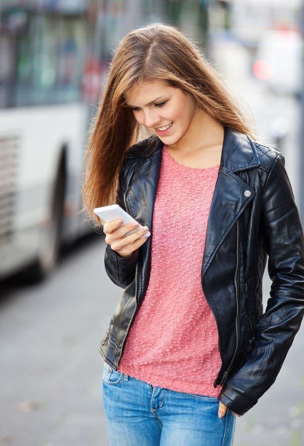 Привлекательная девушка используя ее умный телефон стоковые изображения