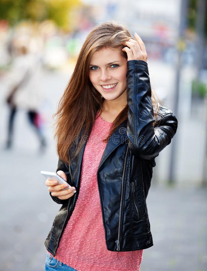 Привлекательная девушка используя ее умный телефон стоковая фотография