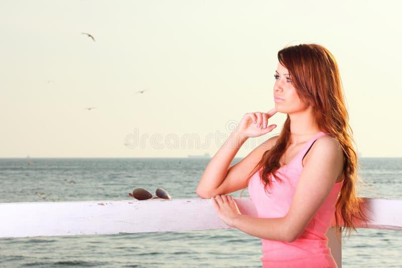 Привлекательная девушка на молодой женщине и море пристани стоковые изображения