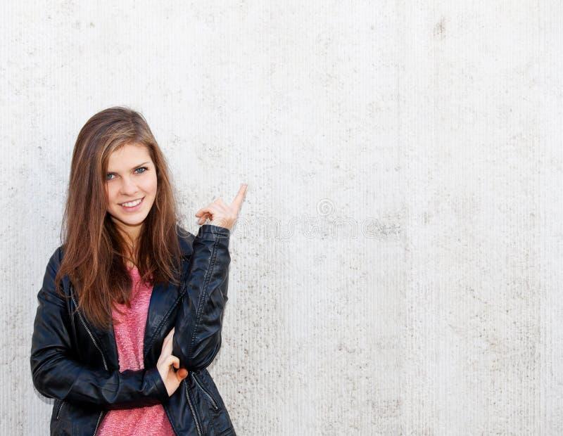 Привлекательная девушка перед бетонной стеной стоковая фотография rf