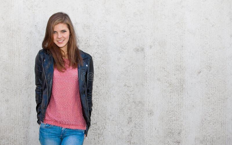 Привлекательная девушка перед бетонной стеной стоковые фотографии rf