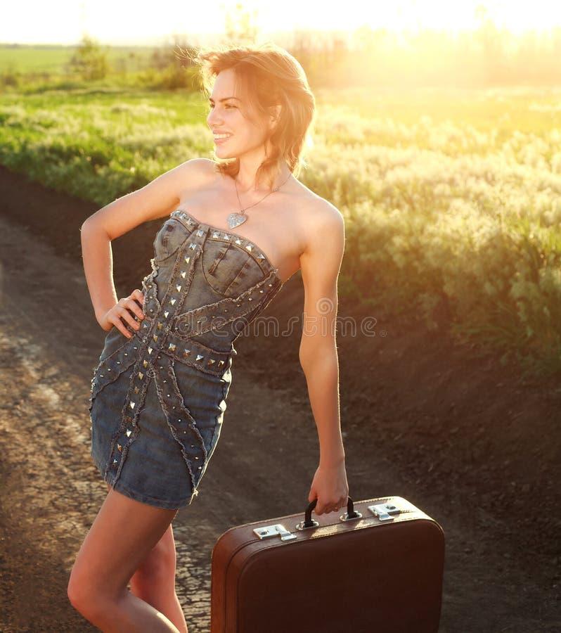 Привлекательная девушка представляя с чемоданом на сельской местности стоковая фотография