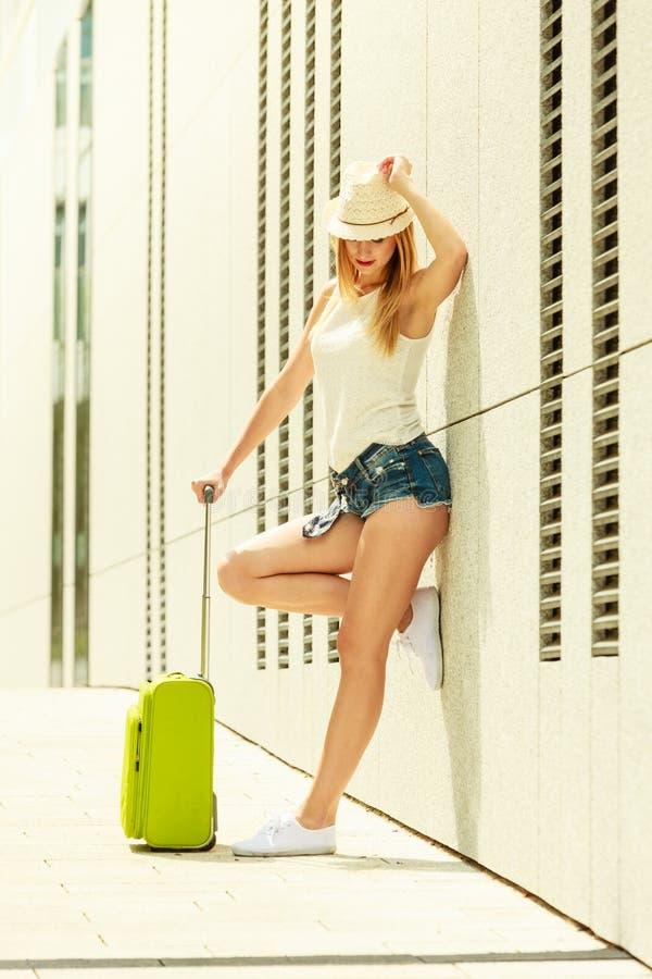 Привлекательная девушка с зеленым чемоданом на улице стоковое изображение