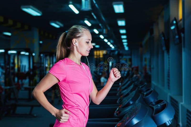 Привлекательная девушка фитнеса бежать на третбане машины Милая девушка делая разминку на современном спортзале фитнеса стоковое фото