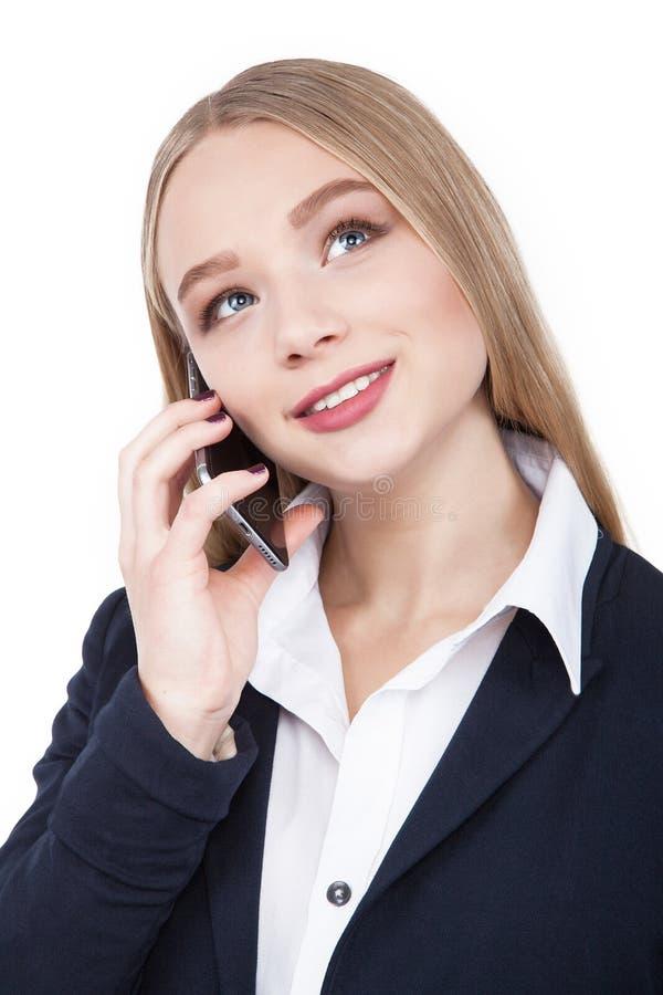 Привлекательная женщина брюнет говоря на ее изолированном сотовым телефоном бело- изображении запаса стоковые фото