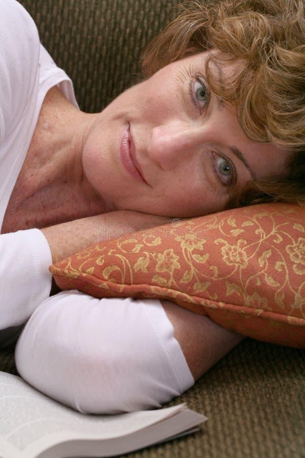 Привлекательная женщина брюнет ослабляя на кресле с книгой стоковые фото