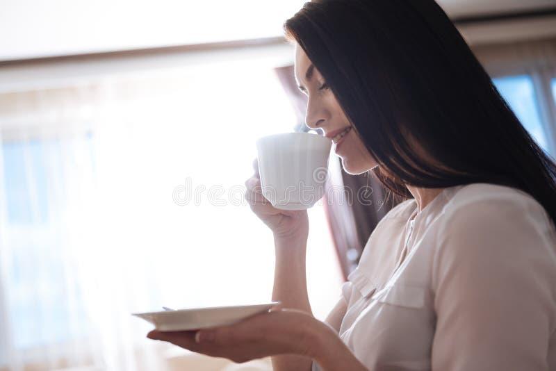 Привлекательная женщина брюнет принимая глоточек кофе стоковая фотография