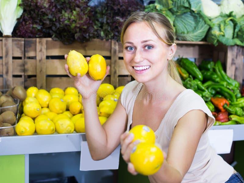 Привлекательная женщина держа лимоны в руках в магазине плодоовощ стоковые фотографии rf