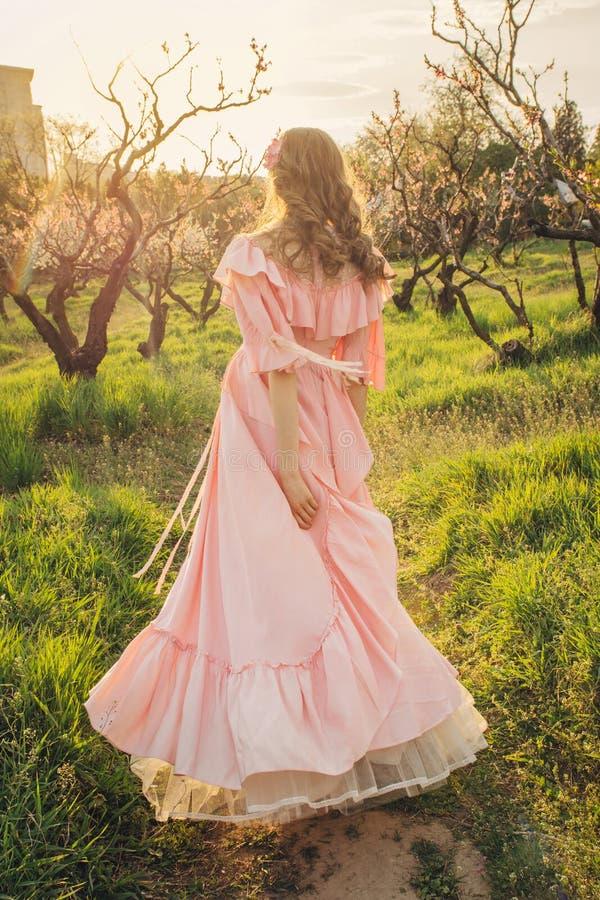Привлекательная женщина идя в сад цветеня на заходе солнца стоковое изображение