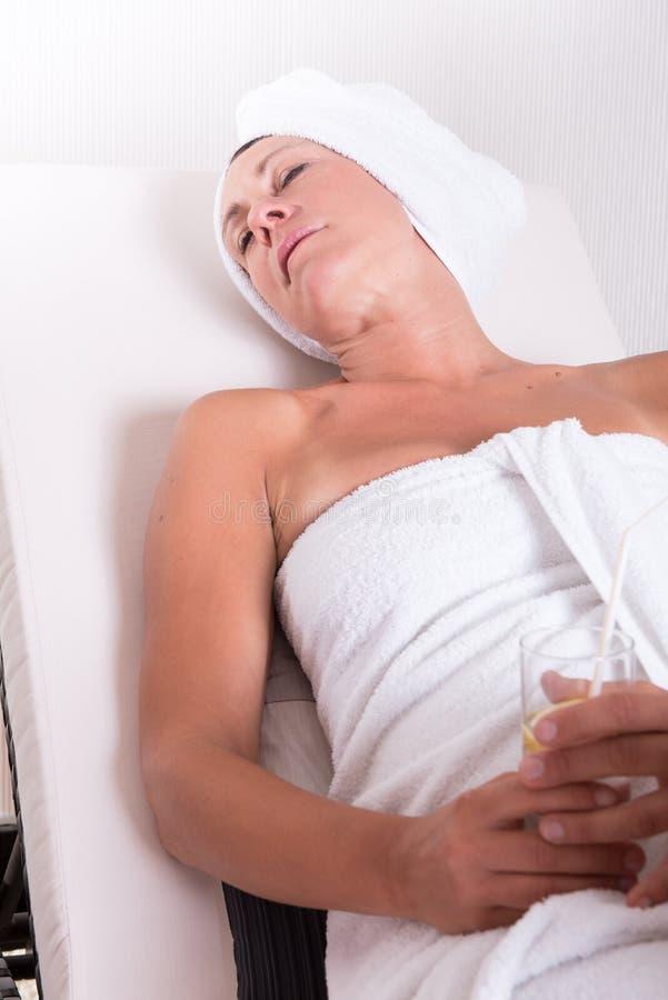 Привлекательная женщина ослабляя после сауны стоковое изображение rf
