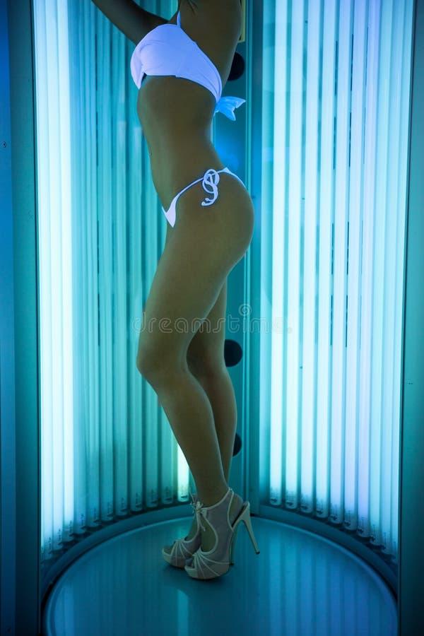 Привлекательная женщина одела в стойках купальника в солярии стоковое изображение