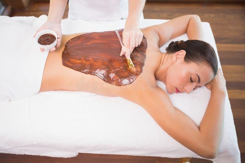 Привлекательная женщина получая маску шоколада заднюю на спа-центре стоковое фото rf