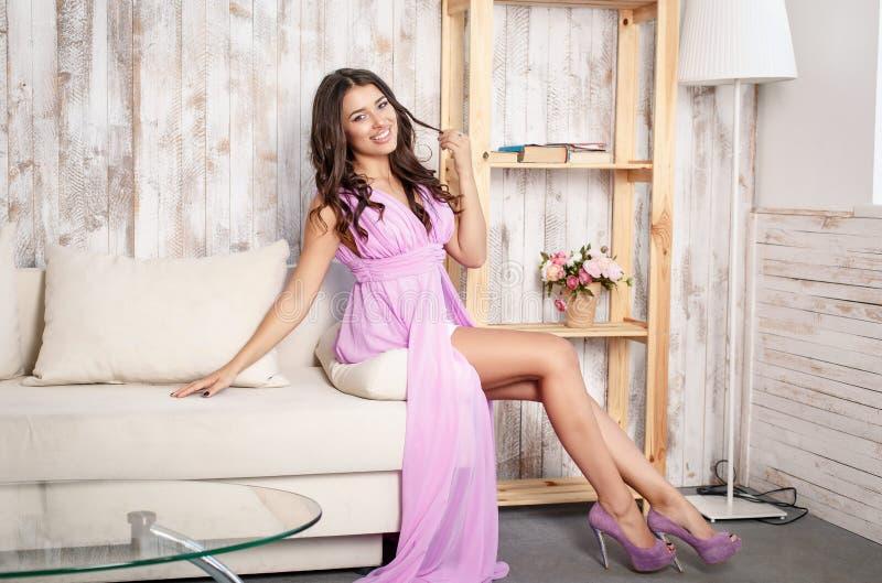 Привлекательная женщина представляя в розовом платье в стиле моды стоковое фото rf