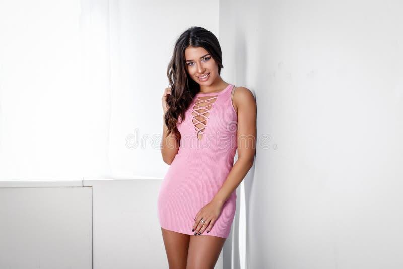 Привлекательная женщина представляя в розовом платье в стиле моды стоковая фотография rf