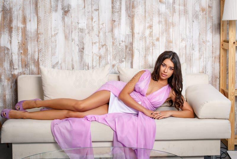 Привлекательная женщина представляя в розовом платье в стиле моды стоковые изображения