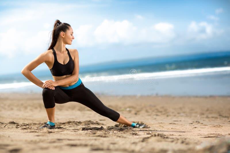 Привлекательная женщина пригонки протягивая на пляже стоковое изображение rf