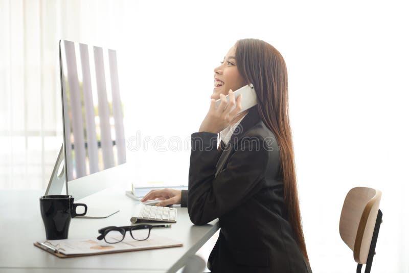 Привлекательная женщина работая в офисе на компьтер-книжке стоковые фото