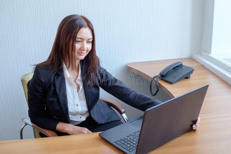 Привлекательная женщина работая в офисе на компьтер-книжке стоковые фотографии rf