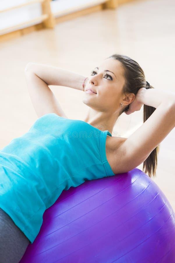 Привлекательная женщина работая с шариком фитнеса стоковая фотография