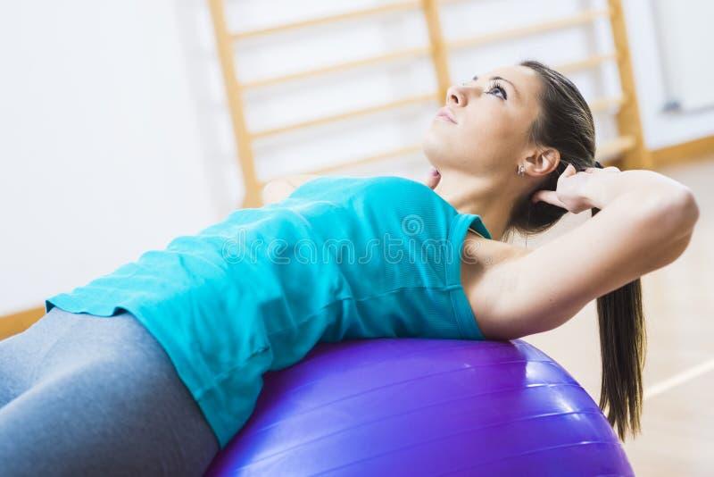 Привлекательная женщина работая с шариком фитнеса стоковое фото