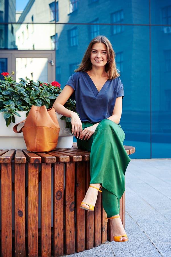 Привлекательная женщина сидя на круглом стенде с цветочным горшком и smil стоковая фотография rf