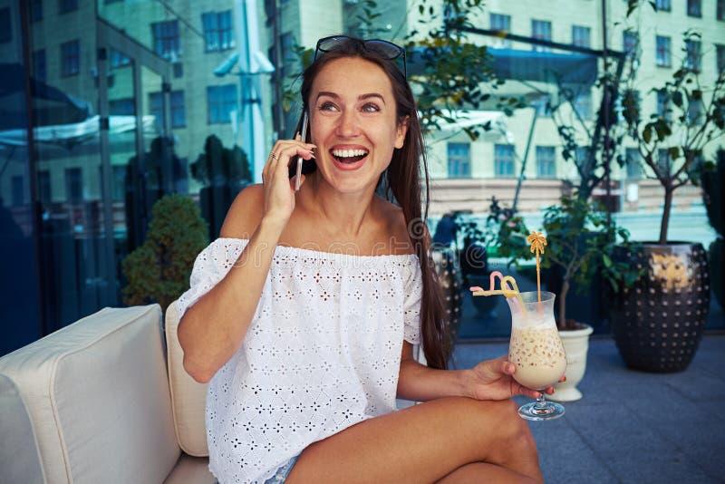 Привлекательная женщина сидя на открытой террасе с коктеилем в ее ha стоковое изображение rf