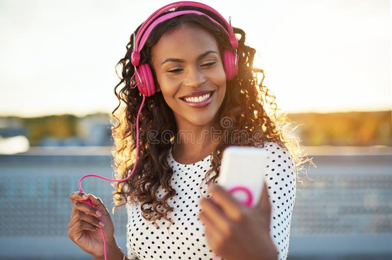Привлекательная женщина слушая к музыке на ее черни стоковые фотографии rf