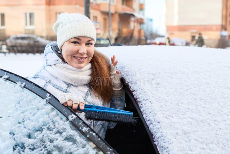 Привлекательная женщина с щеткой снега и снежным автомобилем стоковое фото rf