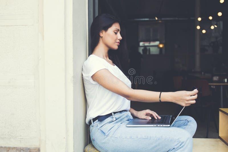 Привлекательная книга чтения девушки битника на портативном компьютере во время завтрака в современной кофейне стоковые изображения