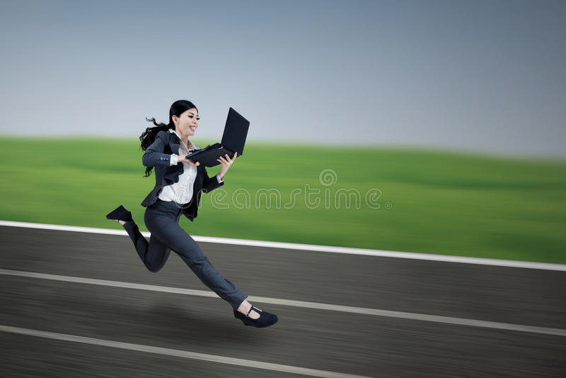 Привлекательная коммерсантка бежать с компьтер-книжкой стоковое изображение rf