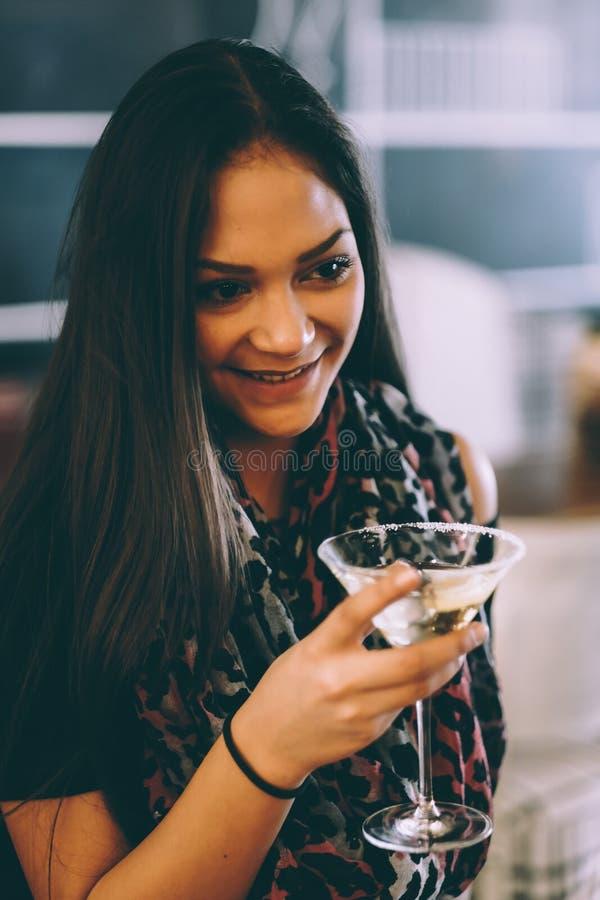 Привлекательная маленькая девочка держа стекло и выпивая Мартини с коктеилем лимона стоковая фотография